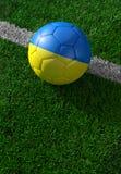 Ballon de football et drapeau national de l'Ukraine, herbe verte Photos libres de droits