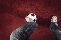 Ballon de football et pied sur un rouge Photographie stock