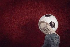 Ballon de football et pied sur un rouge Photographie stock libre de droits
