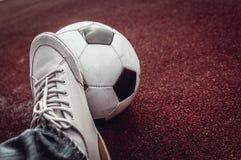Ballon de football et pied sur un rouge Photo libre de droits