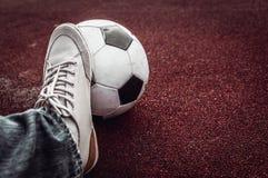 Ballon de football et pied sur un rouge Photos libres de droits