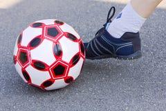 Ballon de football et une jambe des athlètes dans les espadrilles Image stock