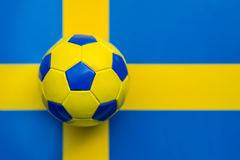 Ballon de football jaune-bleu dans la perspective du drapeau du Royaume de Suède, Image stock