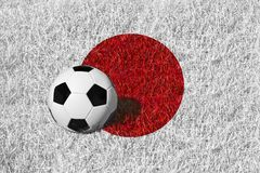 Ballon de football ou boule du football sur champ blanc/rouge, drapeau national du Japon Image libre de droits