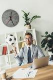 ballon de football de rotation d'homme d'affaires heureux sur le doigt photo stock