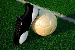 Ballon de football sur la chaussure de champ et de football Photo stock