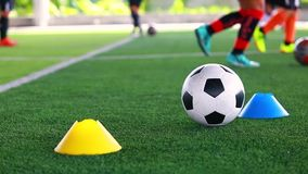 Ballon de football sur le gazon artificiel vert entre le fabricant de cônes avec la formation trouble d'équipe de football banque de vidéos