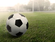 Ballon de football sur un terrain de football d'herbe, sous le coucher du soleil Photographie stock libre de droits