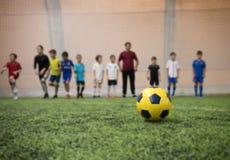 Ballon de football traditionnel sur le terrain de football sur le fond des joueurs de football d'enfants et de leur entraîneur photographie stock libre de droits