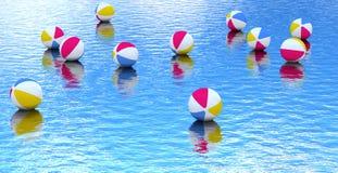 Ballon de plage flottant sur l'eau bleue Photographie stock