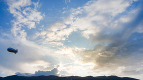 Ballon för heliumlitet luftskeppadvertizing som svävar det solnedgånghimmel och berget royaltyfria foton