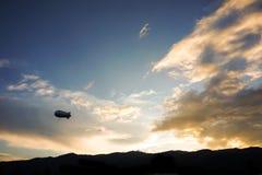 Ballon för heliumlitet luftskeppadvertizing som svävar det solnedgånghimmel och berget Fotografering för Bildbyråer