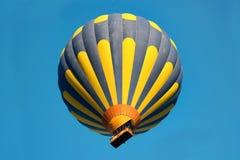 Ballon rayé bleu et jaune dans le ciel Photo stock