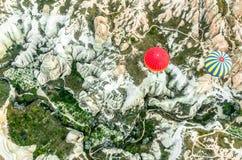 Ballon rouge et ballon avec les rayures jaunes et bleues au-dessus de Cappado image stock