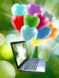 Ballone und Computer auf einem grünen Hintergrund des Grases im Gartenabschluß oben Lizenzfreie Stockfotos