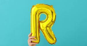 Ballong för beröm för bokstav R för guld- folie lager videofilmer
