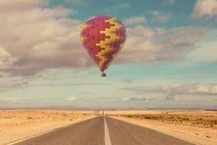 Ballong för varm luft över öken och vägen arkivbilder