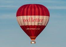 Ballong för varm luft för dagar för röd bokstav med passagerare arkivfoto