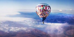 Ballong för varm luft ovanför moln