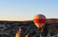 Ballong för varm luft som flyger över dalen på soluppgång cappadocia kalkon royaltyfri fotografi