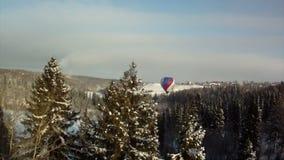 Ballong för varm luft som flyger över snö-täckt skog arkivfilmer