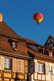 Ballong för varm luft som flyger över tak av Colmar Arkivfoto