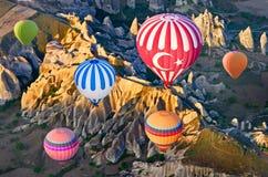 Ballonger för varm luft över berglandskap i Cappadocia, Turkiet Fotografering för Bildbyråer