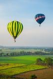 Ballonger för varm luft över grön risfält Royaltyfri Bild