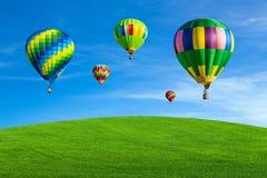 Ballonger för varm luft över grönt fält Arkivfoton