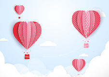 Ballonger för varm luft i form av hjärtaflyget i moln Pappers- konst Royaltyfri Bild