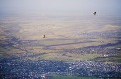 Ballonger för varm luft ovanför det gröna fältet och byarna royaltyfri fotografi