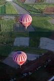 Ballonger för varm luft på soluppgång som flyger över ett lapparbete av fält i den Goreme regionen av Cappadocia i Turkiet Arkivfoton