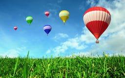 Ballonger för varm luft som flottörhus över grönt fält Royaltyfria Bilder