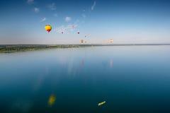 Ballonger för varm luft som flyger över sjön Arkivfoto