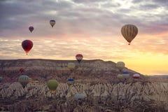 Ballonger för varm luft som flyger för att turnera över berglandskap royaltyfria foton