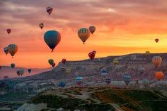 Ballonger för varm luft som flyger för att turnera över berglandskap i morgonen royaltyfri foto