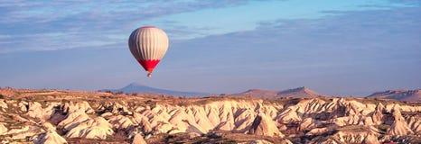Ballonger för varm luft som flyger för att turnera över berglandskap royaltyfri bild