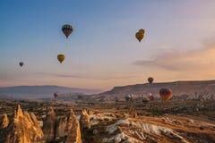 Ballonger för varm luft som flyger i soluppgången över berglandskap Arkivfoto