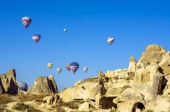 Ballonger för varm luft som hänger över de forntida boningarna av Cappadocia, Turkiet Royaltyfria Bilder