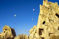 Ballonger för varm luft som hänger över de forntida boningarna av den magiska Cappadociaen, Turkiet Royaltyfria Foton