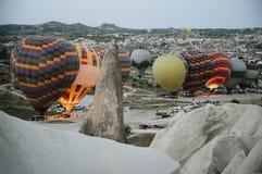 Ballonger f?r varm luft som landar i en bergCappadocia Goreme nationalpark Turkiet royaltyfria bilder