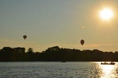 Ballonger f?r varm luft ?ver en sj? i den Polen sikten under solnedg?ng arkivbild
