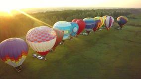 Ballonger flyger upp i himmel med passagerare över grönt fält fotografering för bildbyråer