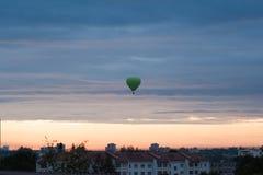 Ballonger flyger upp i himmel med passagerare ?ver gr?nt f?lt E r royaltyfria bilder