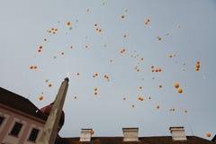Ballongfrigörare av den vita och orange ballongen bredvid kyrkligt - önskakort royaltyfria foton