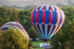 Ballons à air chauds étant gonflés pour se préparer à un lancement de début de la matinée images libres de droits