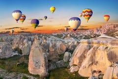 Ballons à air chauds au coucher du soleil au-dessus de la ville de caverne, Cappadocia Image libre de droits