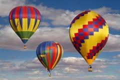 Ballons à air chauds colorés dans un ciel nuageux Image stock