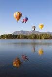 Ballons à air chauds colorés volant au-dessus d'un lac Photos stock