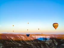 Ballons à air chauds colorés volant au-dessus de la vallée chez Cappadocia Photographie stock libre de droits